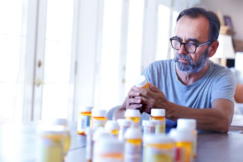 A latino baby boomer sits at his dining room table and sorts through various prescription medications as sunlight filters in through the window behind him bathing the room with a soft glow of light.