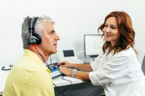 A Caucasian senior man at medical examination or checkup up with a hearing specialist.
