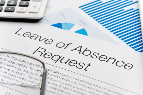 Leave of absence request form on a desk with paperwork. Close up.