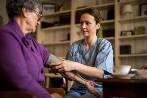 Young Caucasian female nurse taking a senior woman's blood pressure in a home library setting.