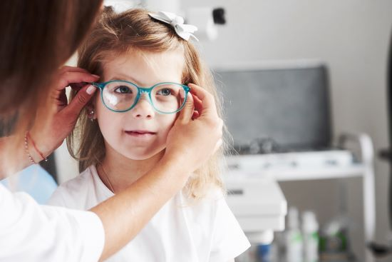 Caucasian female child being fitted for her new glasses.