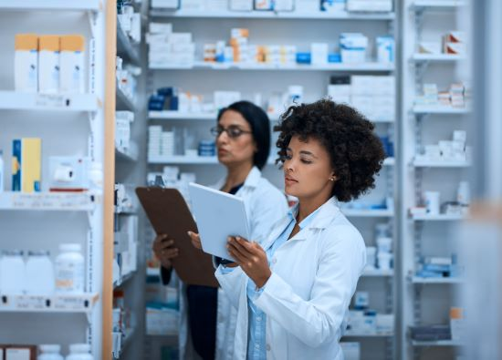 Driving a high performing pharmacy with teamwork - stock photo shot of a young woman doing inventory in a pharmacy on a digital tablet with her colleague in the background.