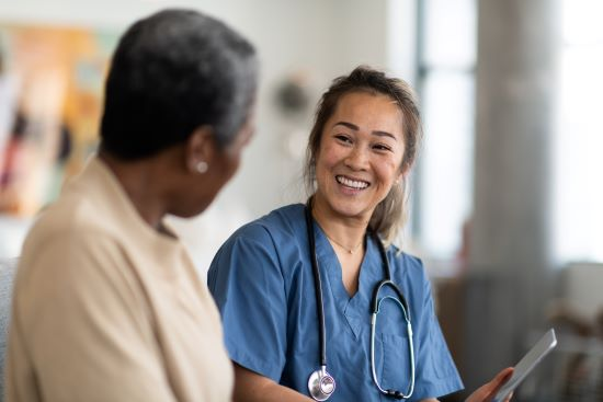 Female nurse and female patient having a conversation - The nurse wears a stethoscope around her neck and is holding a tablet computer