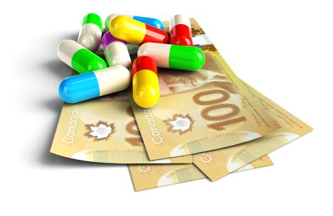 Colorful pill capsules on New Canadian 100 hundred dollar bills to present the high cost of drugs.
