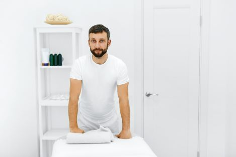 Caucasian male massage therapist standing and leaning forward with his hands resting on the massage table.