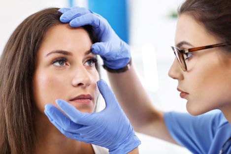 Picture of adult woman having her eye examined by a female doctor.