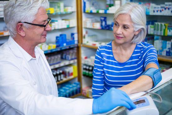 Male Pharmacist checking blood pressure of female customer in pharmacy