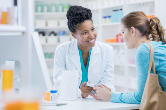 A Black female pharmacist provides medication instructions to a white female patient.