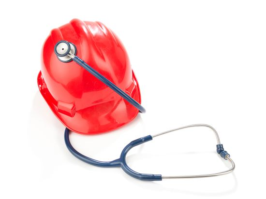 Work place safety concept with red hard hat and stethoscope isolated on white background.