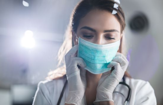 Young female doctor putting on protective mask