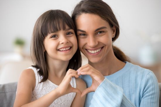 Cute little daughter and happy mother join hands in shape of heart as concept of mom and child love care support, smiling mum and her kid girl looking at camera posing together for headshot portrait - used to represent healthy and happy, and great smiles thanks to good dentistry.