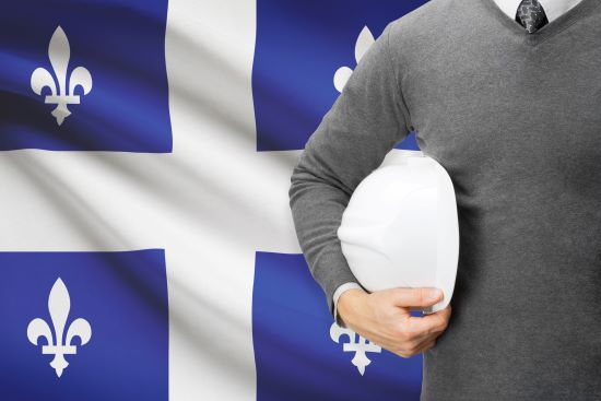 Torso of a Caucasian man holding a white hard hat standing in front of a Quebec flag.