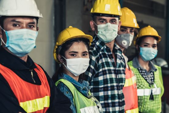 Diverse group of factory workers with face mask protect from outbreak of Corona Virus Disease 2019 or COVID-19.