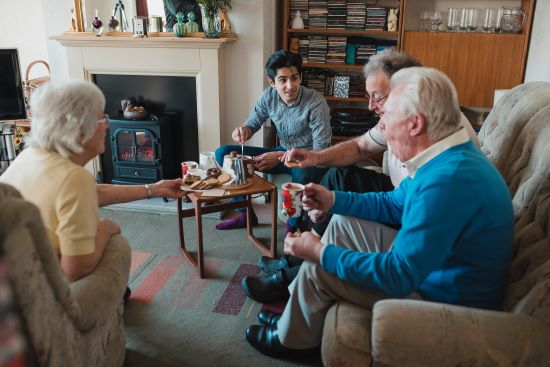 A teenage boy is assisting senior adults having tea at a nursing home.