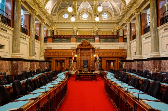 An image of the throne and desks inside the British Columbia legislature.