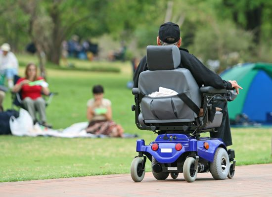 A man suffering from amyotrophic lateral sclerosis enjoying a ride in the park in his electric wheelchair.