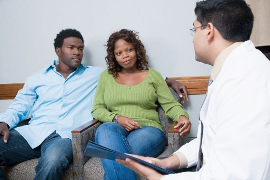 A Black couple consulting with a doctor in a private medical clinic.