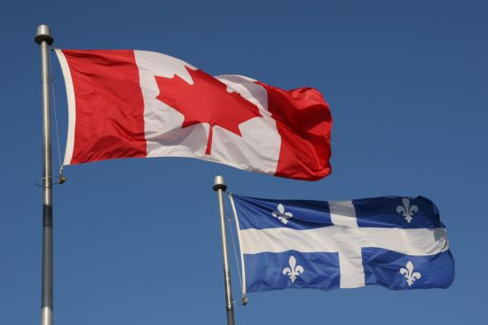 The Canadian and Quebec flags flapping in a breeze against the backdrop of a deep blue sky.