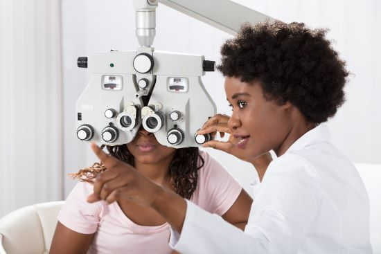 A Black Female Optometrist conducting a sight examination on a black female patient.