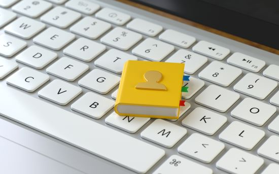 A yellow address book sitting on a white computer keyboard representing an online directory to search for doctors in British Columbia.