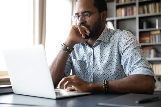 Thoughtful millennial biracial man in eyeglasses staring at laptop screen contemplating a difficult decision.