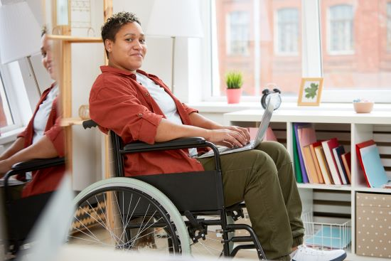 A young black woman is sitting in a wheelchair working on a laptop in a workplace.