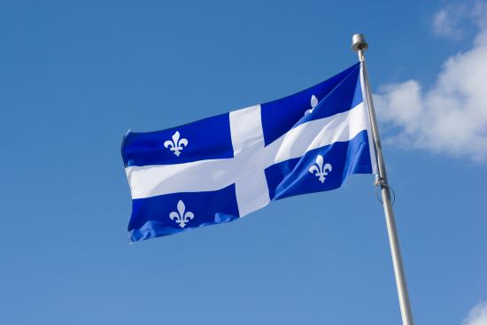 Quebec flag waving in a breeze set on a blue sky background with fluffy white clouds.
