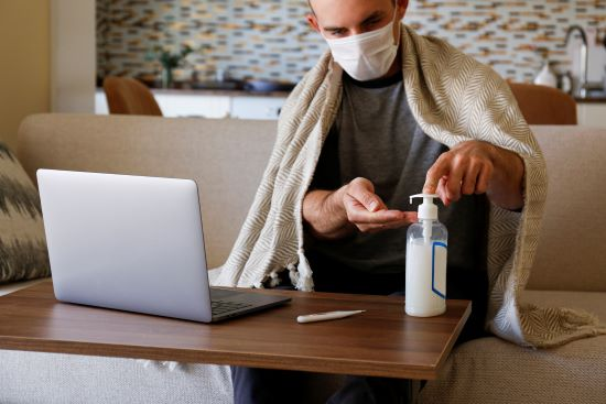 A caucasian male sitting on his sofa with a blanket draped over his shoulders. He is wearing a mask and cleaning his hands with sanitizer. A laptop and digital thermometer sit on the table in front of him.